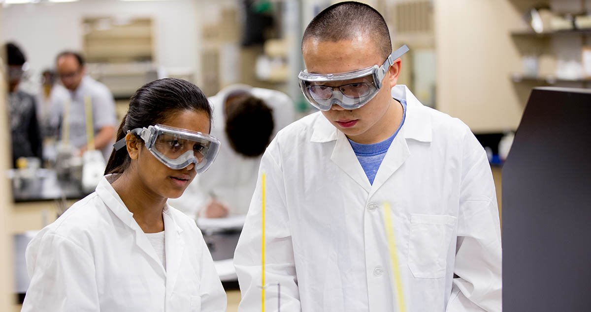 Photo of undergrad students in white lab coats